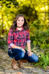 Brown haired girl kneeling in garden for senior session at tryphenas garden in middle georgia for senior photography session