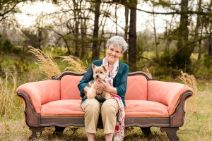 lady in green shirt sitting on sofa in field holding puppy for portrait session middle georgia