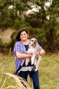 lady in blue and pink shirt holding her puppy in field for portrait session middle georgia