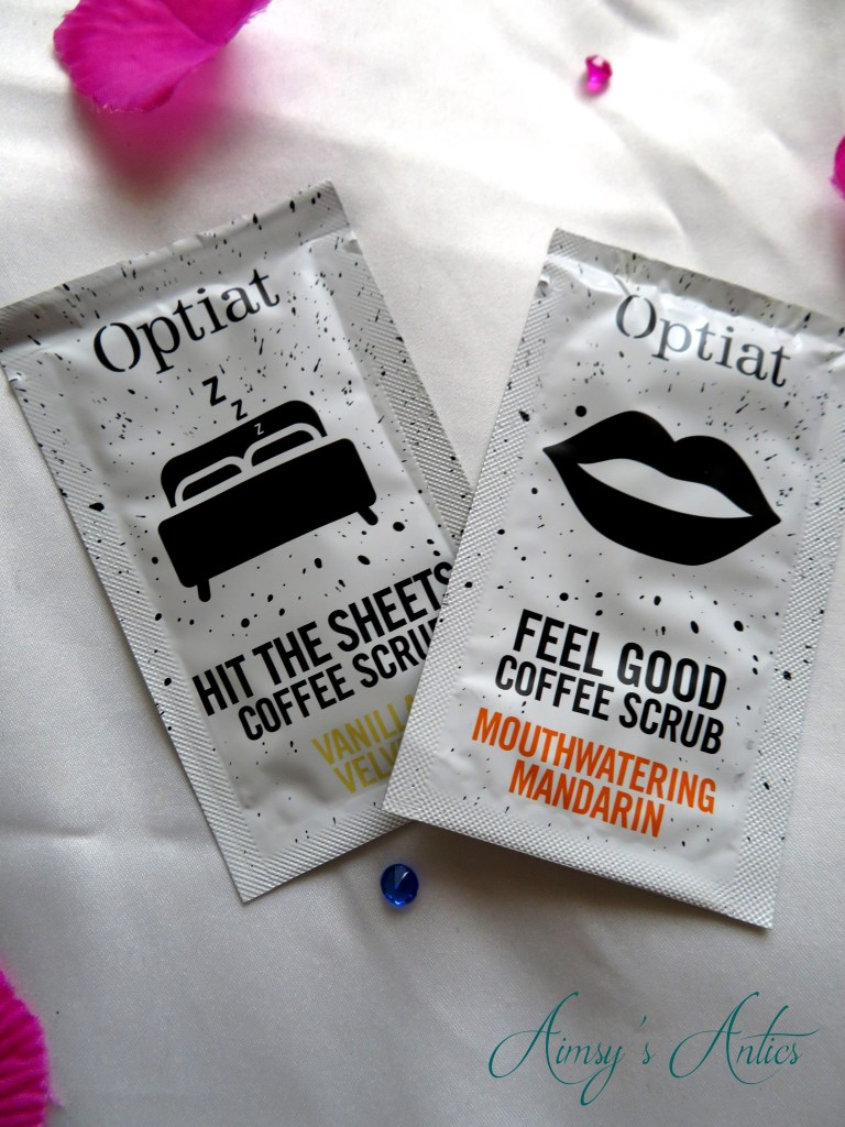 """Two packets of Optiat coffee scrubs. Named """"Hit the sheets coffee scrub"""" and """"Feel good coffee scrub""""."""
