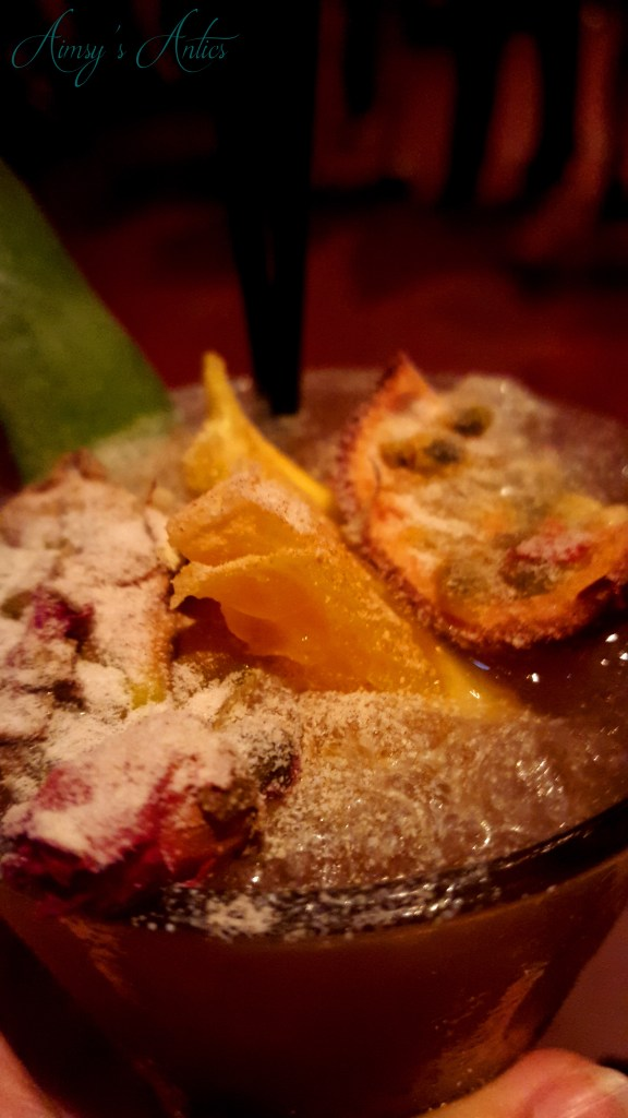 Image of Cocktail with passionfruit, orange and rose decoration, dusted with icing