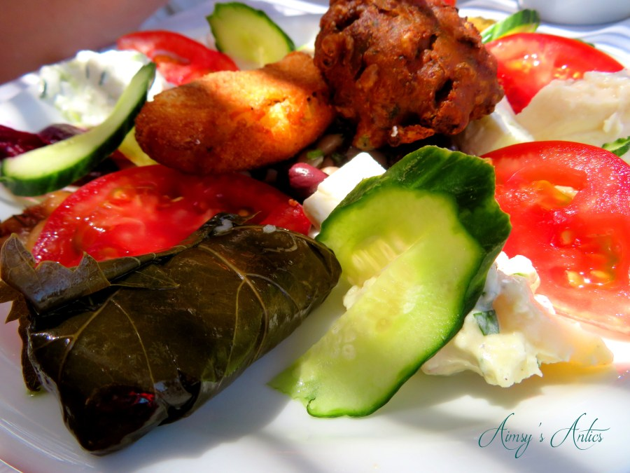 Image of Greek food - mixed starter, including stuffed vine leaves, frittas, cucumber and tomatoes