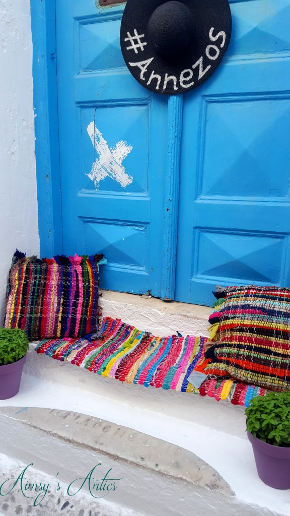 Image of a Mykonos shop with multicoloured rug and cushions on the step and a hat with the words 'Annezos' on.
