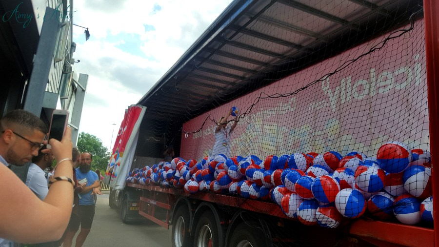 Girl holding up the winning beach ball in a lorry filled with beach balls at Ice Lolly's blog at the beach event