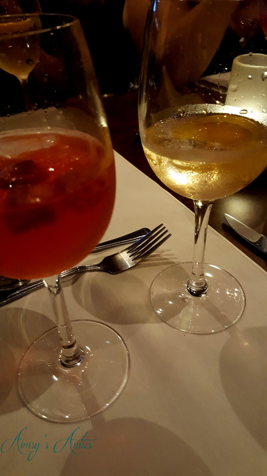 Two glasses of flavoured gin on a table with garnishes of orange and raspberries