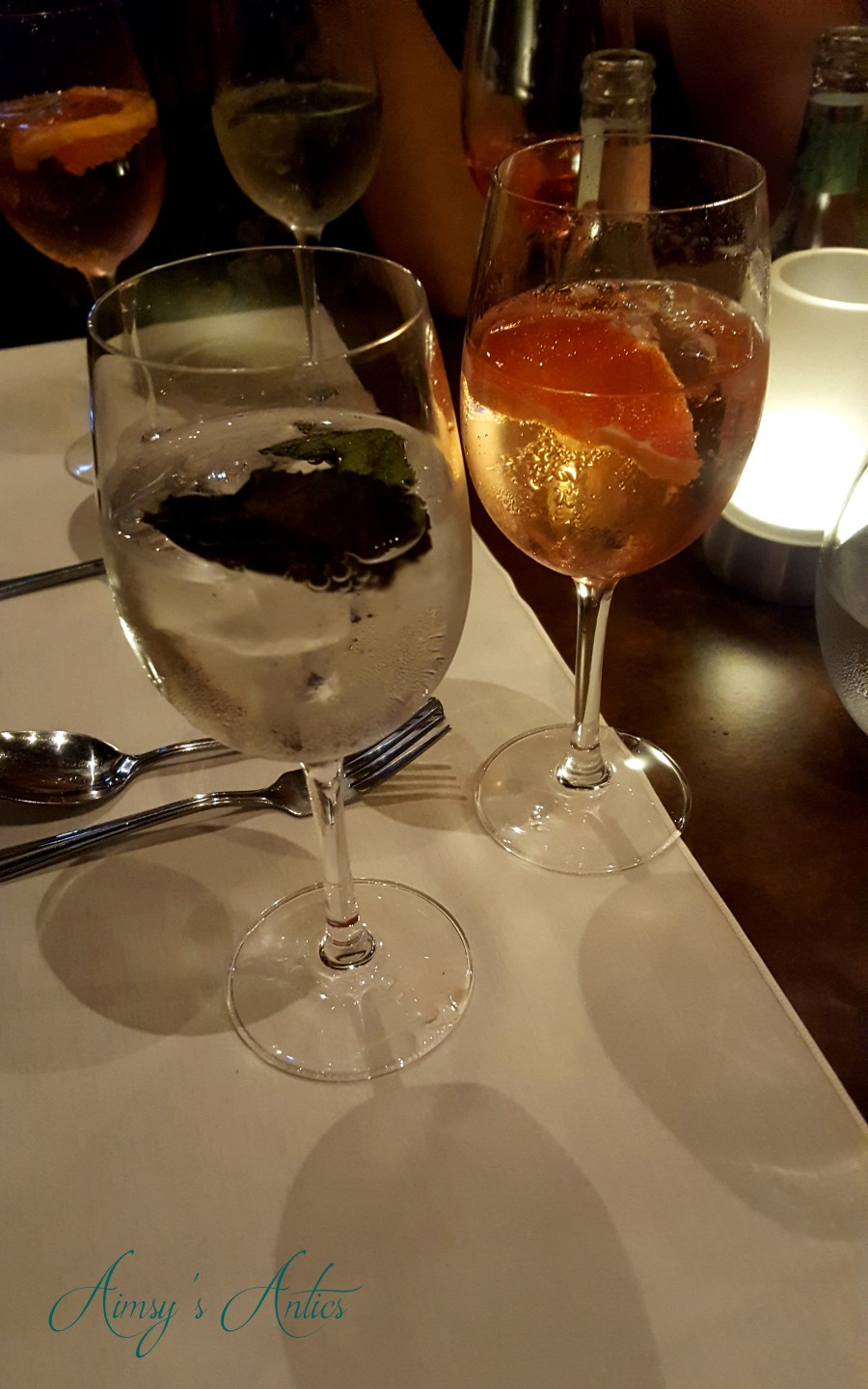 Two glasses of gin on a table with grapefruit and mint leaves garnishes