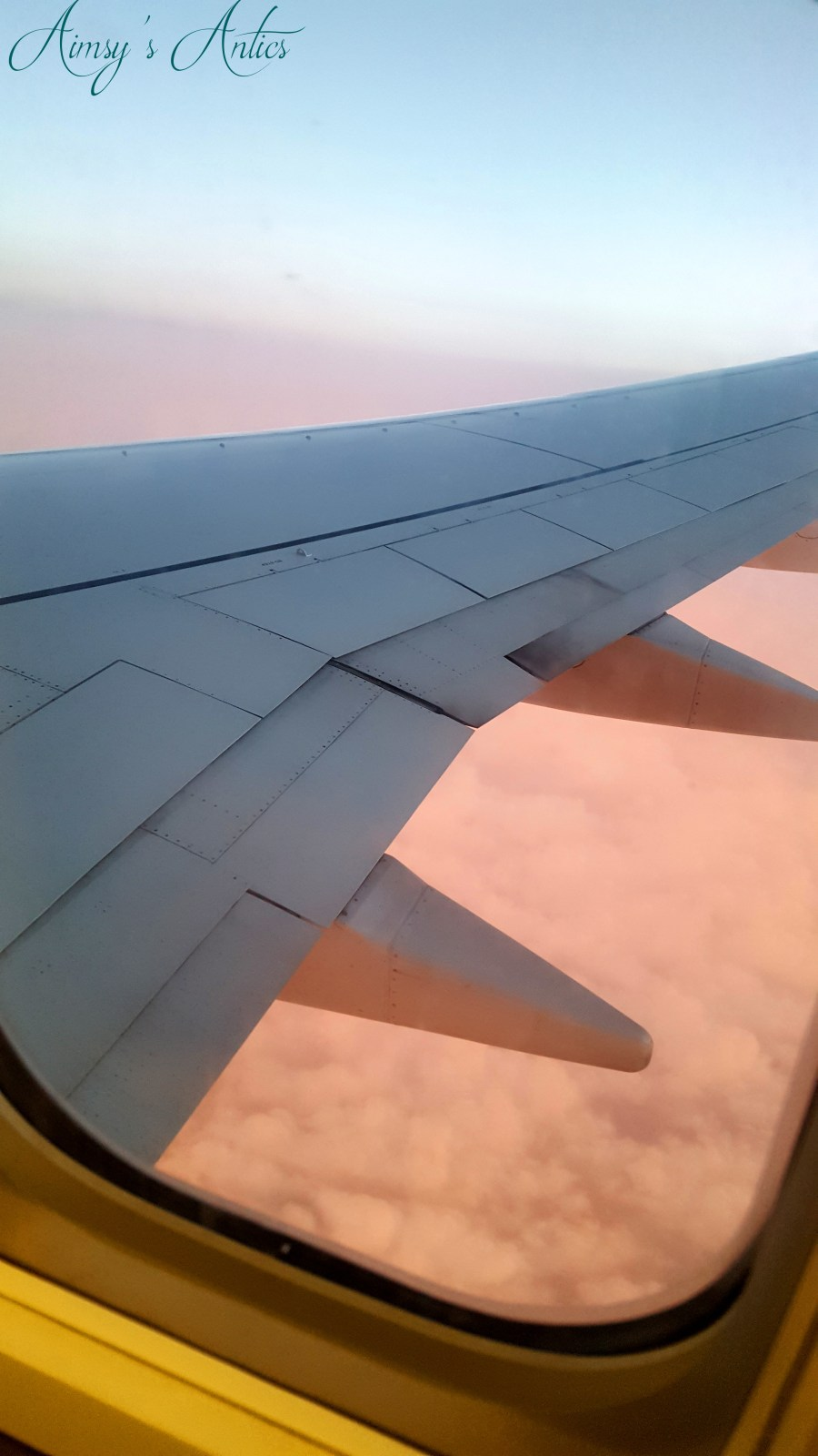 View of a aeroplane wing from the window. Clouds with orange glow below