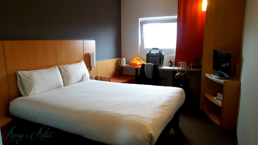 Image of a double bedroom at Ibis Hotel Leeds. Double bed, tv, wardrobe and window in the shot, as well as traveller's belongings.