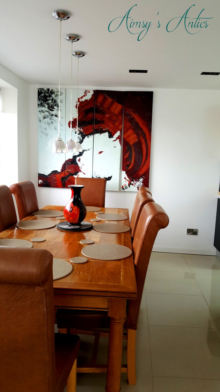 Image of a dining table with gold placemats and red, white and black artwork on the wall in the High -end bechside house