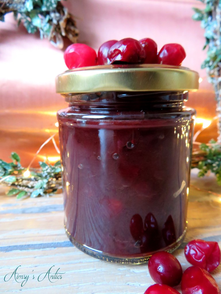 Image of a jar of cranberry and red onion relish, with cranberries on the lid and scattered in front. Christmas heart wreath and fairy lights behind the jar.