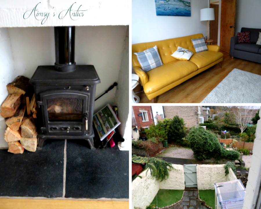 Grid of 3 photos; 1 of a wood burner, 2 of a yellow sofa in a living room, 3 the view of the backyard. All photos from Fernleigh cottage, grange-over-Sands in the Lake District