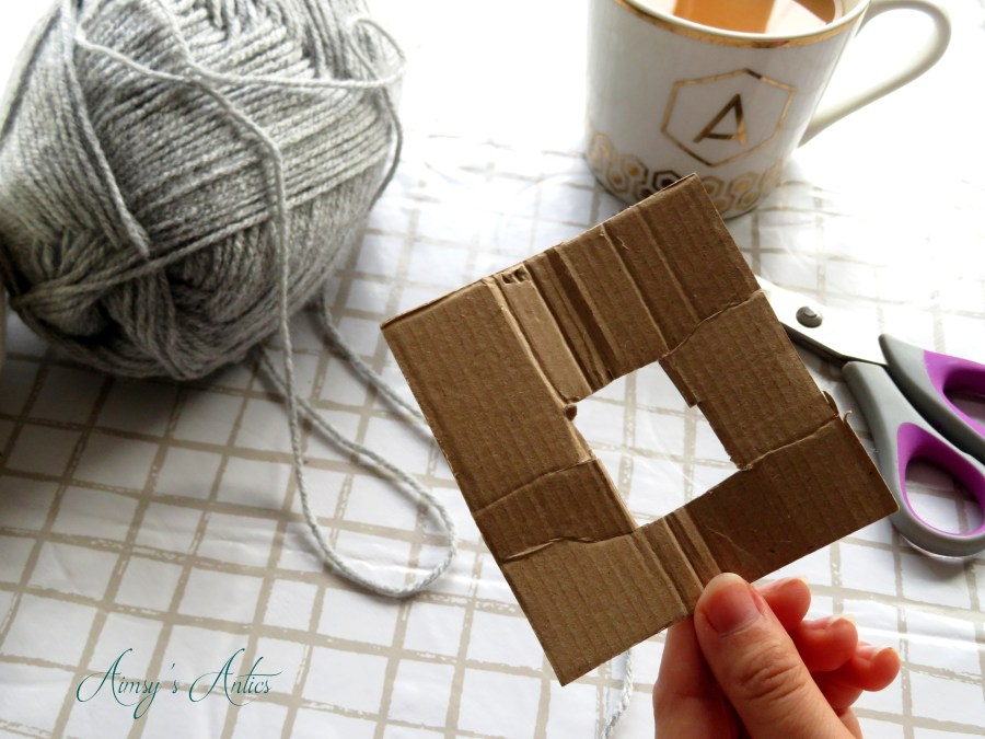 Square cardboard pom-pom template being held in a hand with a ball of grey wool, cup of tea and scissors in the background.