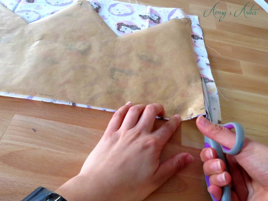 Hands cutting out material aroud the crown shaped template/pattern with sewing scissors.