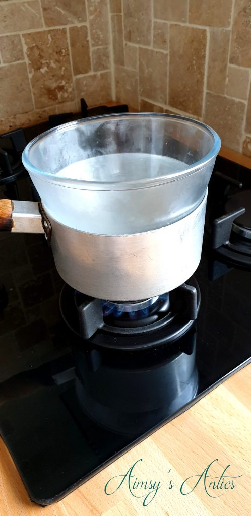 Pan ontop of a stove with a glass bowl on top (Ban-Marie style)
