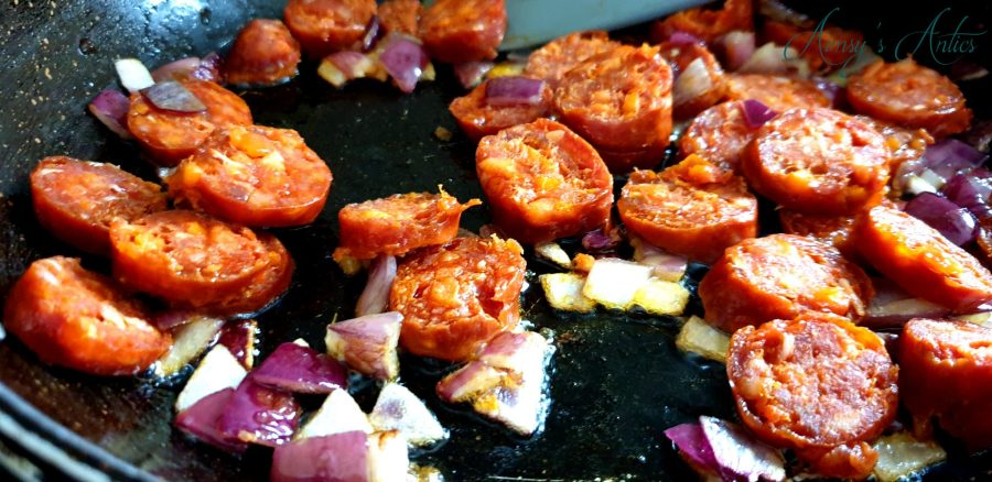 Chorizo cooking in a pan with red onions. Close up shot