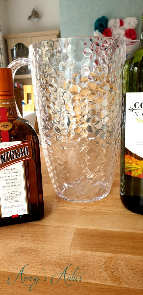 Empty jug with white wine on the right and a bottle of Cointreau on the left