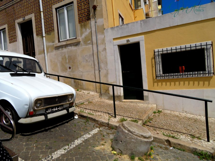 Lisbon street with yellow walls and yellow and brown tiles, with an old car half in shot. Slight diagnol slope to the shot