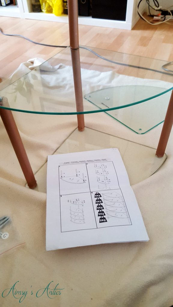 Glass shelving unit being assembled with paper instructions