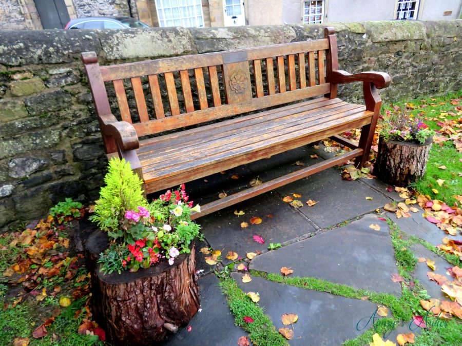 Wooden bench with flowers inside tree trunk planters, wet from rain