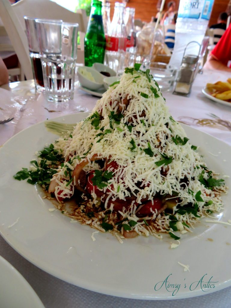 A large salad built up on a plate with grated cheese covering it