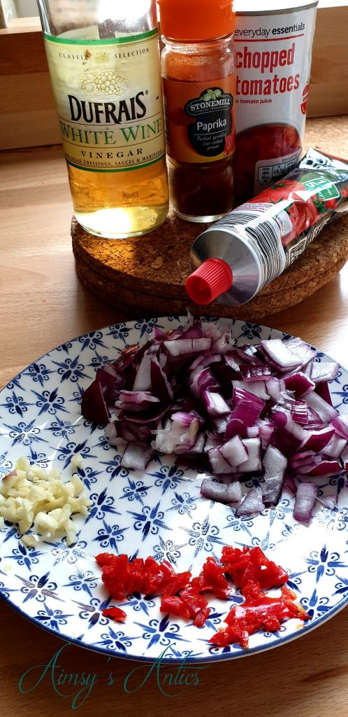Onions, garlic and chilli on a side plate with a tine of chopped tomatoes, tomato puree, paprika and white wine vinegar in the background