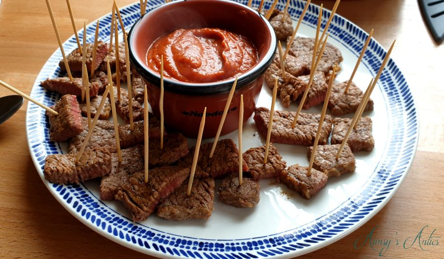 Steak bites with wooden cocktails sticks through them. Chilli sauce in the middle of the plate in a seperate dish.