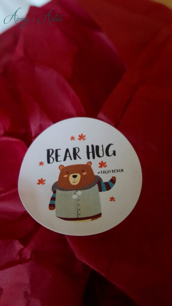 """Round sticker with a cartoon bear on, with the words """"Bear Hug"""" on it"""