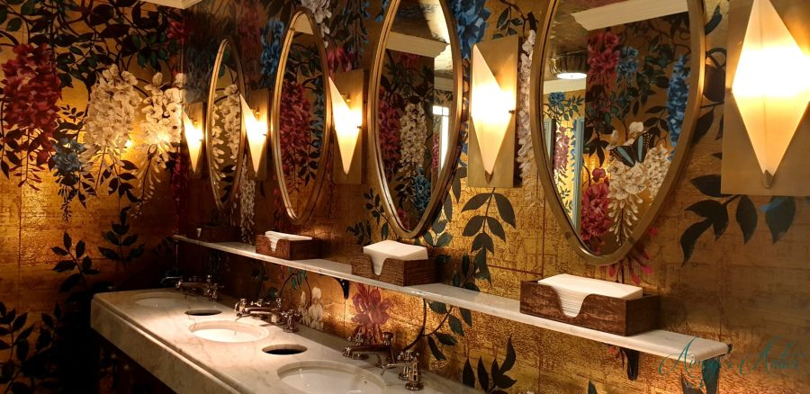 Gold and flower printed tiles with gold rimmed mirrors and sinks underneath