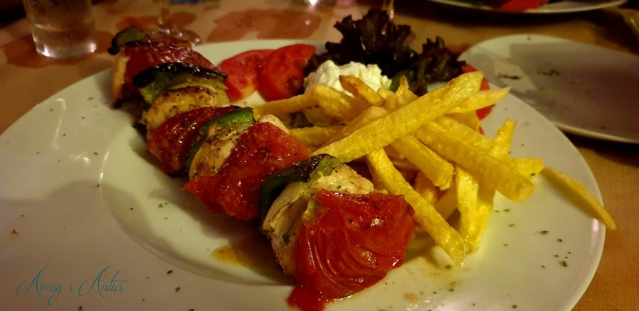 Chicken souvlaki with onions, tomatoes and peppers, also with chips, salad and tzatziki