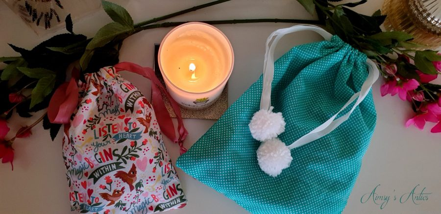 Two drawstring bags and a candle. View from above
