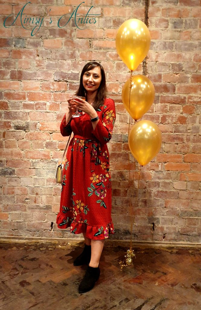 Woman stood infront of a brick wall, with a cocktail in hand, three gold balloons to the right.
