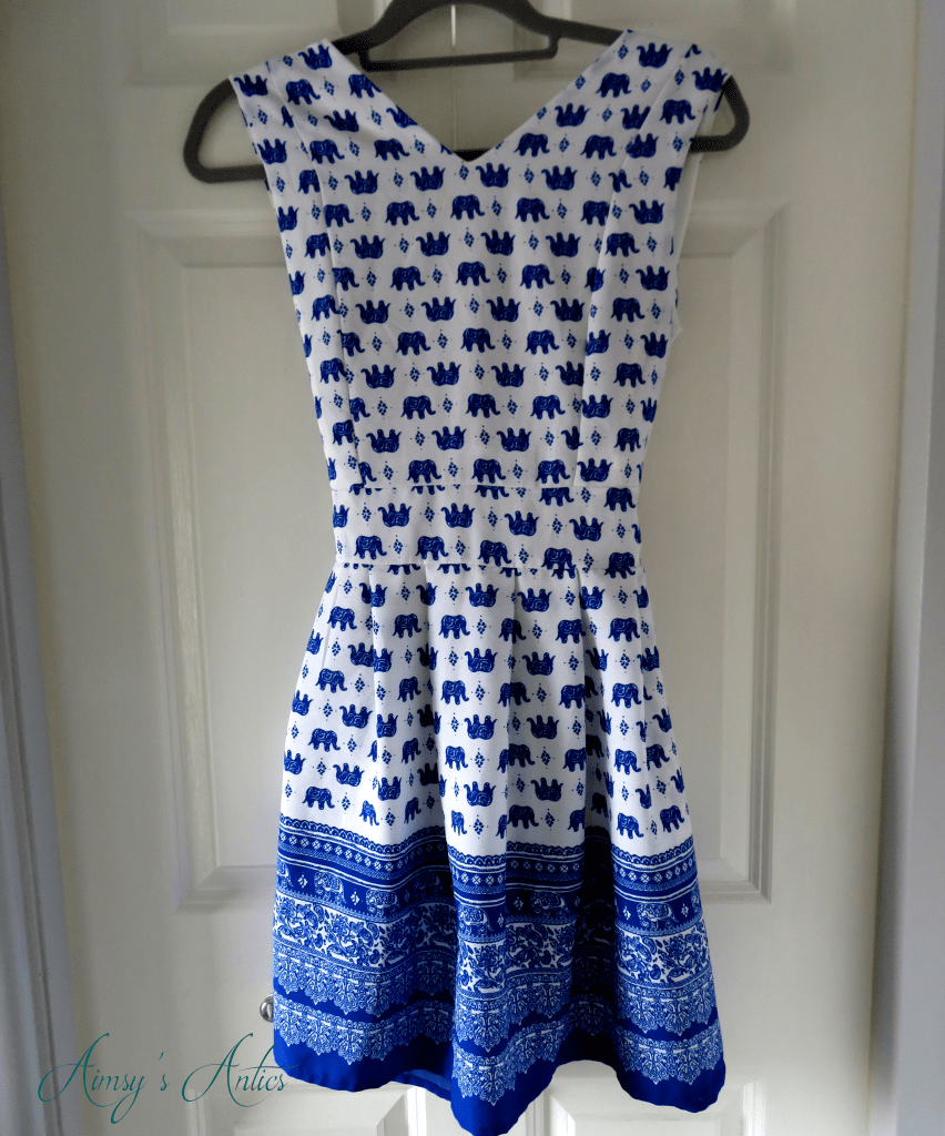 Blue and white elephant print dress hanging from a clothes hanger