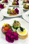 A beautiful Amuse Bouche trio includes Filet of Beef Crostini with Caramelized Onions, Horseradish and Tomato; Asian Tuna Tartar In Cucumber Cups with Ponzu and Micro Wasabi, and Black Caviar Canapé with Sliced Egg and Herbed Cream Cheese.