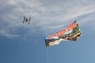 Towing of an aerial advertisement by quadcopter
