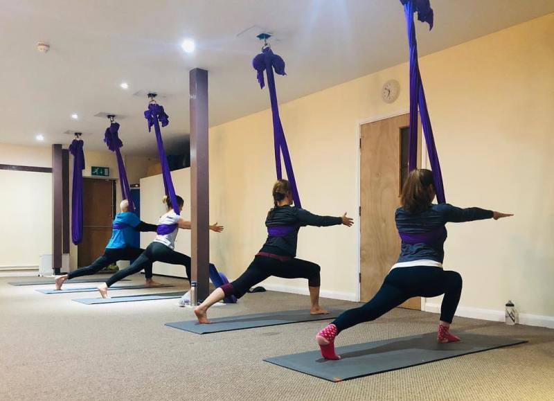 Four people use aerial hammocks to support a lunge position showing the studio as bright and simple in design.