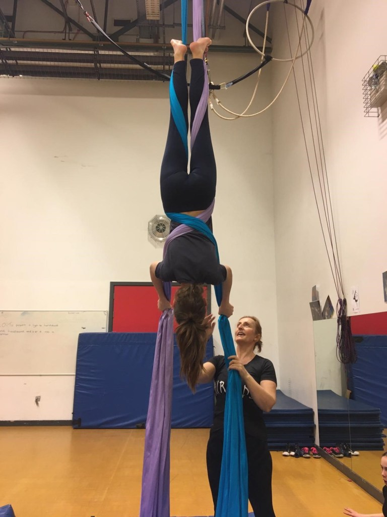 A young aerialist hangs upside down on fabrics supported by teacher, Tina Carter.