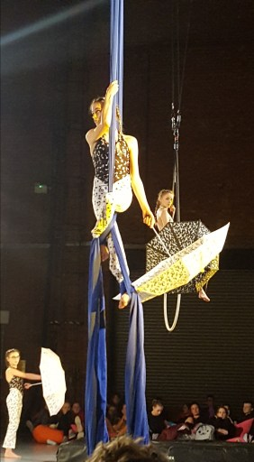 Three girls hold open umbrellas mid-performance. Two are suspended in the air, the other looks on from the floor.