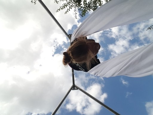 Image of upside down woman hanging from white aerial fabric, outside.