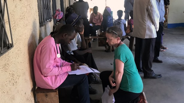 A nurse in the DRC talking with a Congolese medical worker in a health center.