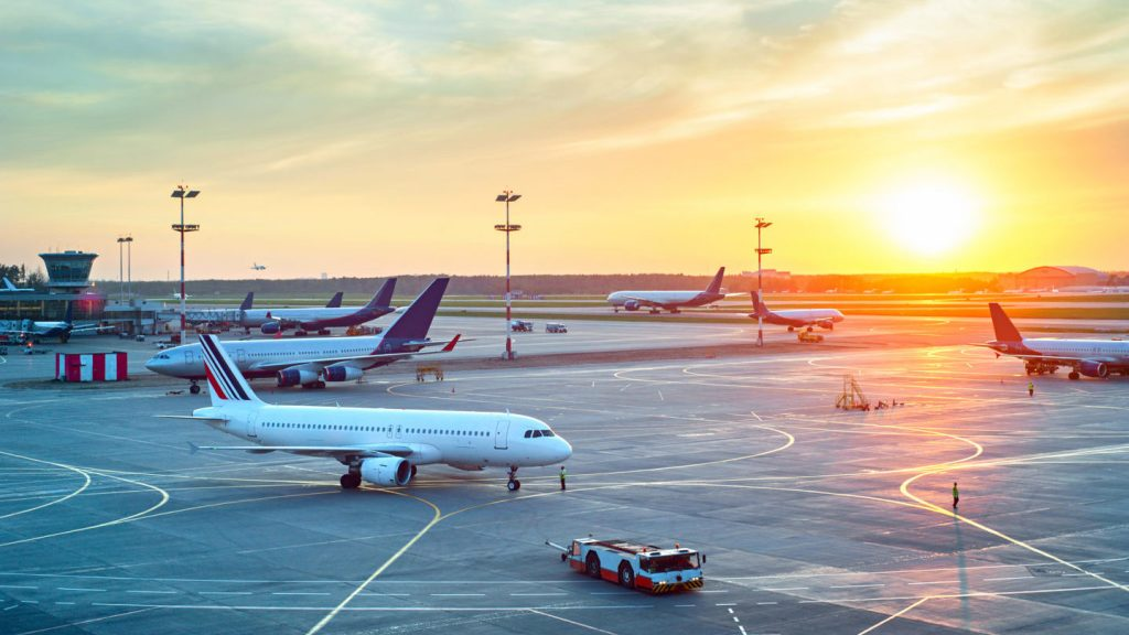 Sunrise over airplanes on airport tarmac