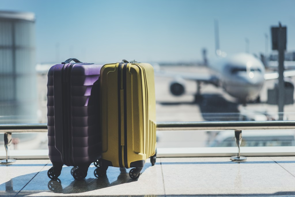 Suitcases in front of airplanes at airport gate