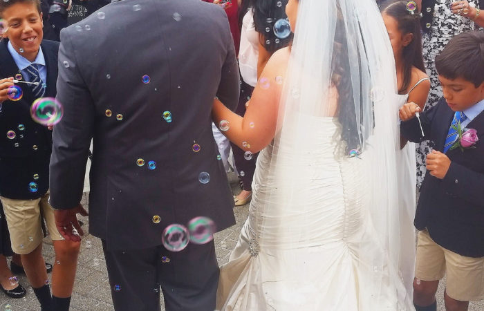 Newlyweds walking as people around them blow bubbles