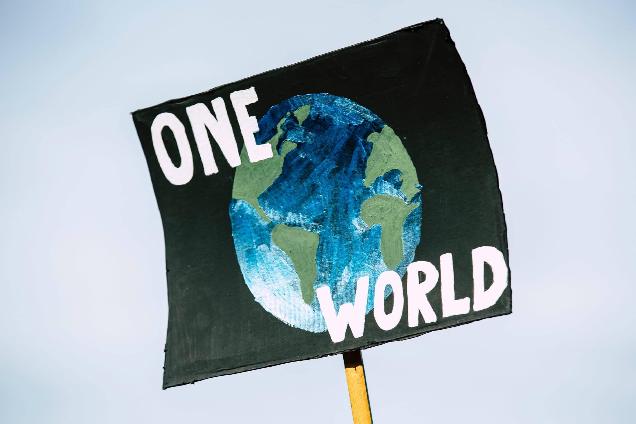 Cardboard placard saying one world