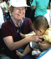 photo of the author, Christine Whitten, as she examines an impatient baby during a volunteer surgical team trip to Vietnam