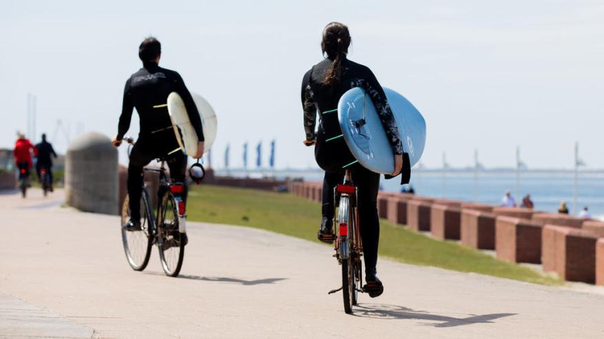May 26th, 2020, Lower Saxony, Norderney: Two surfers on bicycles ride their surfboards along the promenade along the sea. Photo: Rolf Vennenbernd / dpa +++ dpa-Bildfunk +++