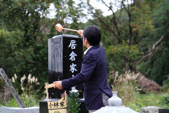 居倉家の墓石に箕輪町から組んできた清水をかける将生さん。