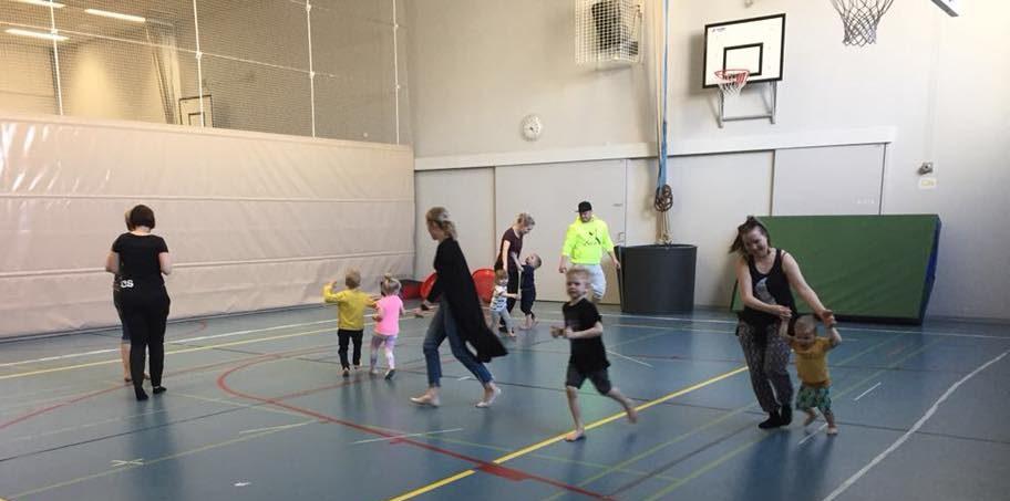Naureskelevat lapset juoksevat iloisesti mukana pysyttelevien aikuisten edellä ympäri salia.