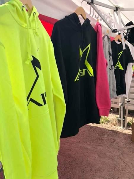Täytekuvassa Aisti-huppareita fluminon, mustan, pinkin ja harmaan värisinä. Taustalla myös mustia t-paitoja.