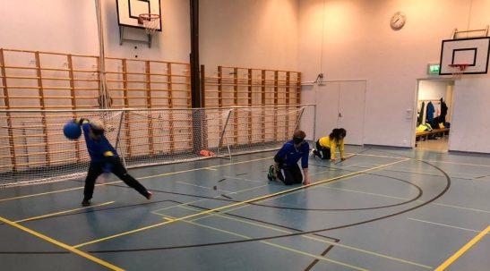 Pelitilannekuva edestäpäin, jossa nuori poika lähtee heittämään palloa vanhempien pelikavereiden valmistautuessa seuraavaan palloon.