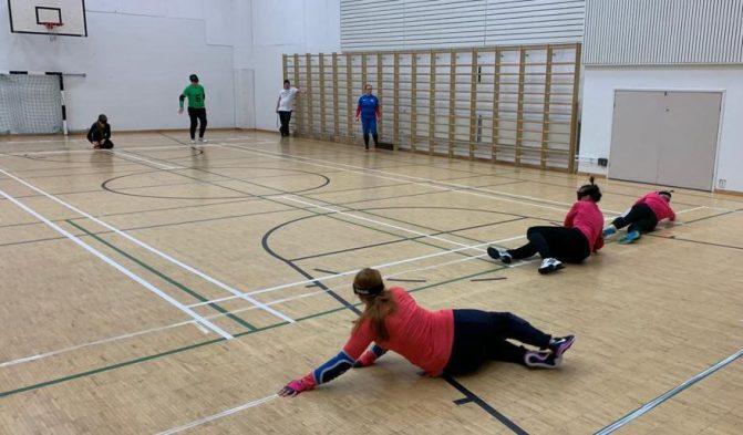 Tilannekuva takaapäin harjoituksista, jossa kolme pinkkipaitaista nuorta naista heittäytyy torjunta-asentoon.